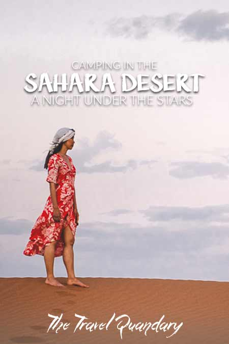 A woman in a red dress stands on a sand dune under the early moon at dusk, Sahara Desert Morocco