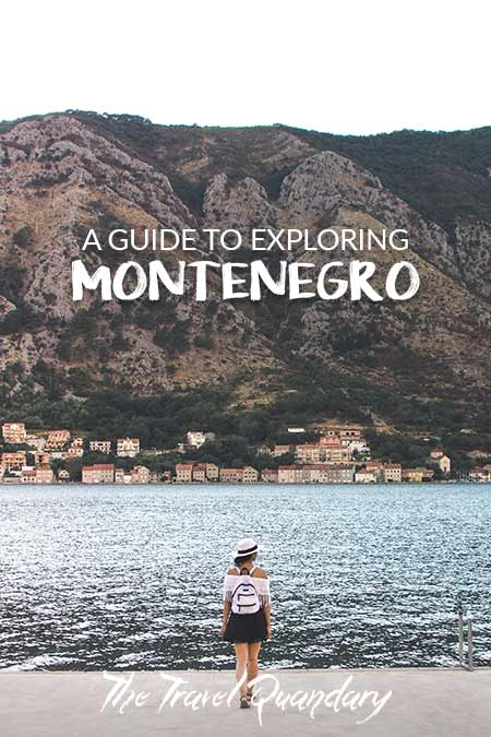 A woman with a white hat and white backpack stands on the edge of the water overlooking the Bay of Kotor, Montenegro