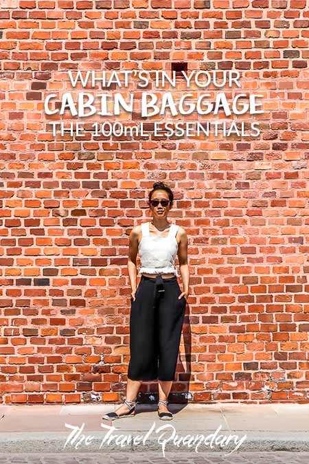 Jasmine of The Travel Quandary poses in front of a red brick wall in Krakow, Poland | Cabin Baggage Liquids Allowance