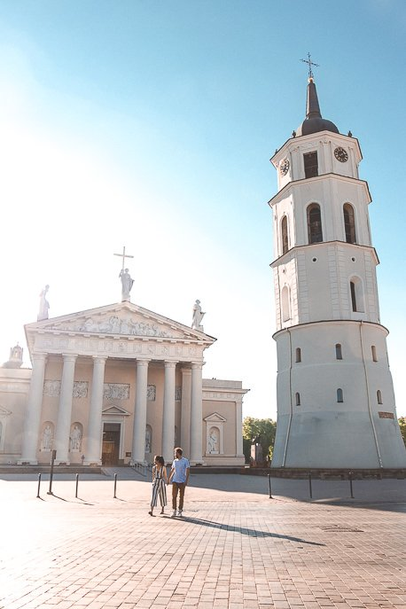 A couple crossing the road in front of Vilnius Cathedral, Vilnius Lithuania