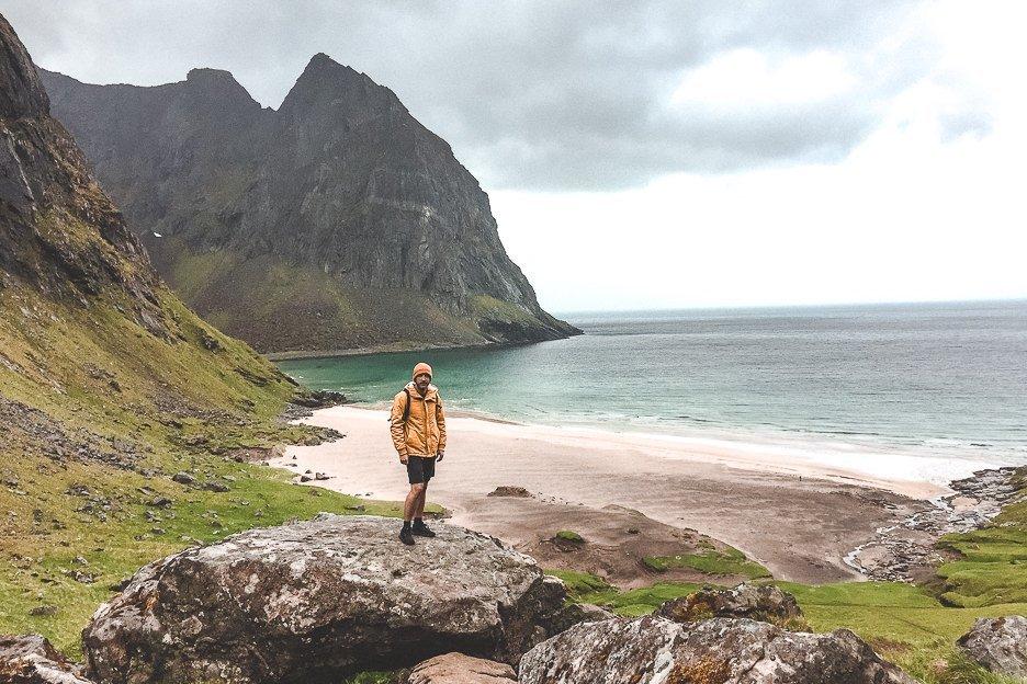 Bevan standing on a rock with Khalika Beach in the background - Lofoten Islands, Norway