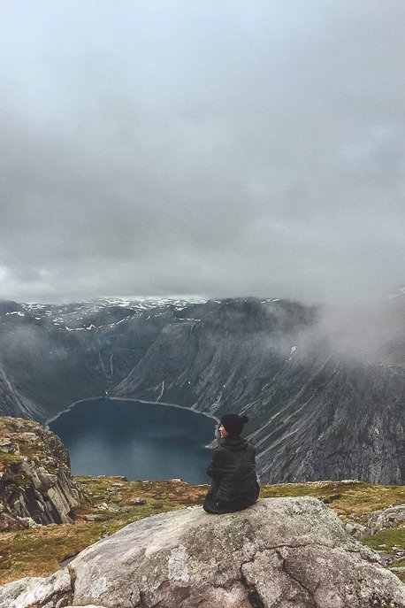 Jasmine sitting on a rock taking in the fjord views - Trolltunga, Norway