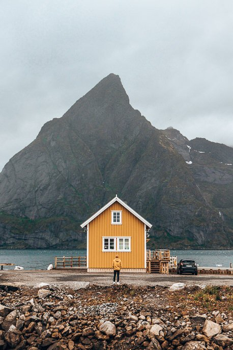 Bevan matching in his yellow coat with the yellow house in Hamnoy - Lofoten Islands, Norway