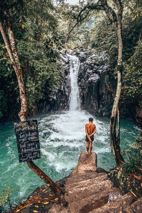 A local boy observes the water from the jumping platform at Kroya Waterfall, Bali Gallery