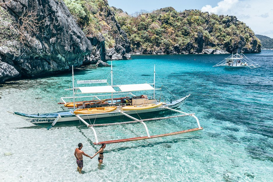 A couple hold hands next to their tour boat in the water on Paradise Beach, El Nido