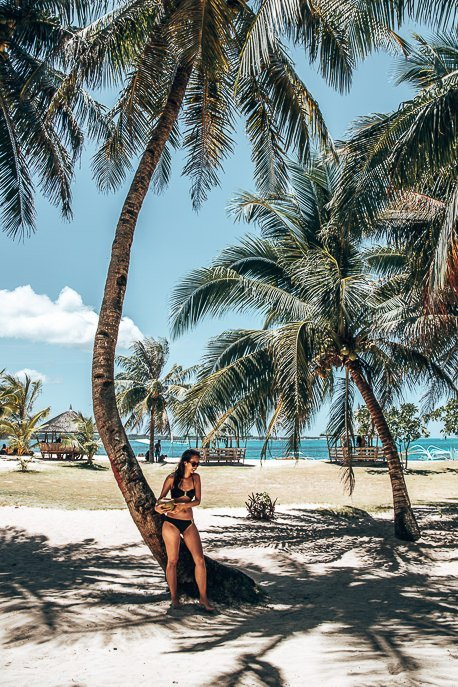 A girl in a black bikini holds a coconut standing in the shade of palm trees on Daku Island