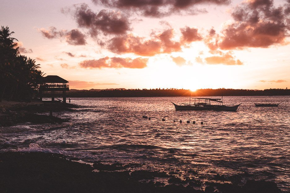 The sun sinks over the horizon with a lone boat on the water of Cloud Nine, Siargao