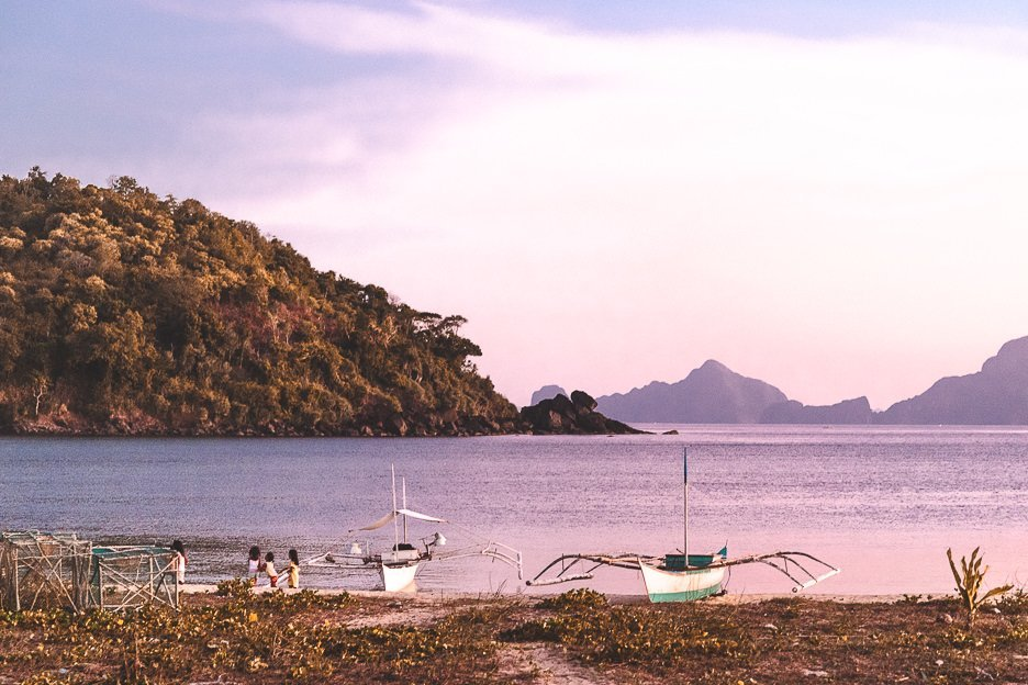Young girls playing by the water next to two boats at Nacpan Beach during sunset, El Nido