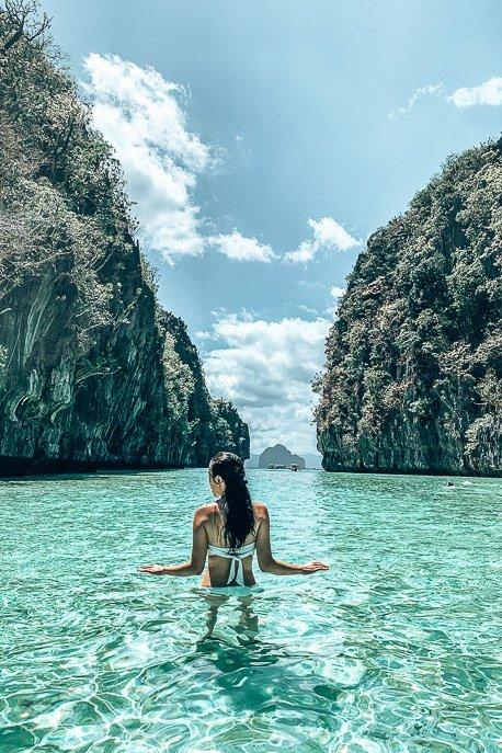A woman wades through the turquoise water at the entrance of Big Lagoon, El Nido