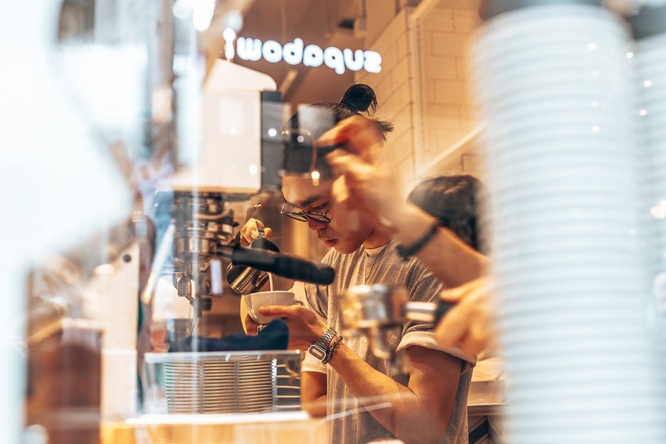 Watching a barista through the glass window meticulously prepare a cup of coffee inside NOC Coffee - Graham Street, Hong Kong