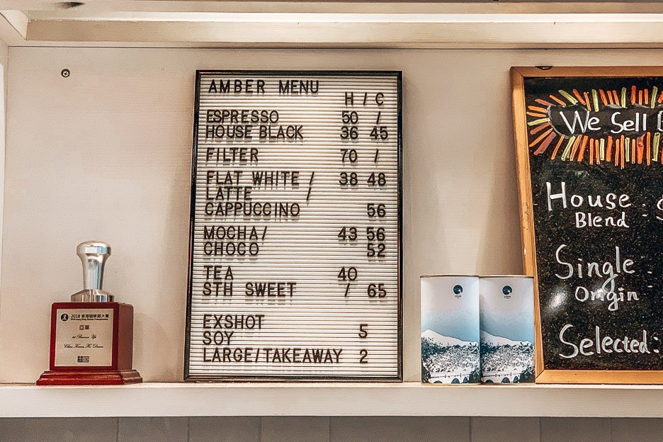 The coffee menu at Amber Coffee Brewery next to its trophies, Hong Kong