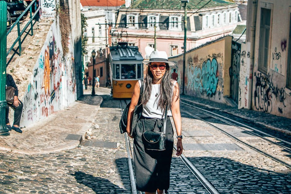 Walking up a cobblestoned hill in front of a yellow tram in Lisbon, Portugal