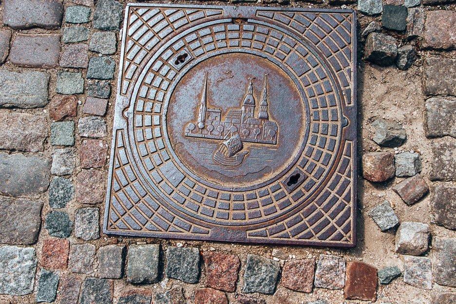 Engraved manhole on the cobble stone streets of Riga, Latvia
