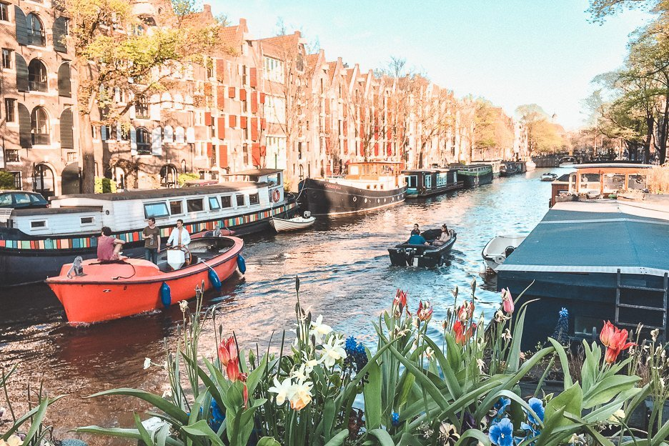 Houseboats and flowers along a canal in Amsterdam, The Netherlands
