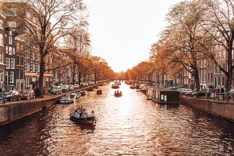 Boats cruise along the canals during sunset in Amsterdam, The Netherlands