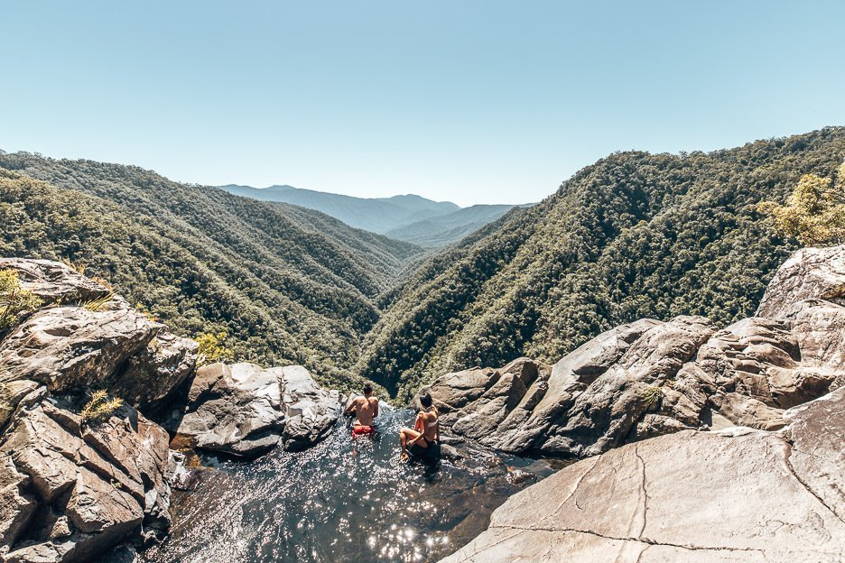 A couple perch on the edge of the infinity pool at the top of Windin Falls in Tropical North Queensland