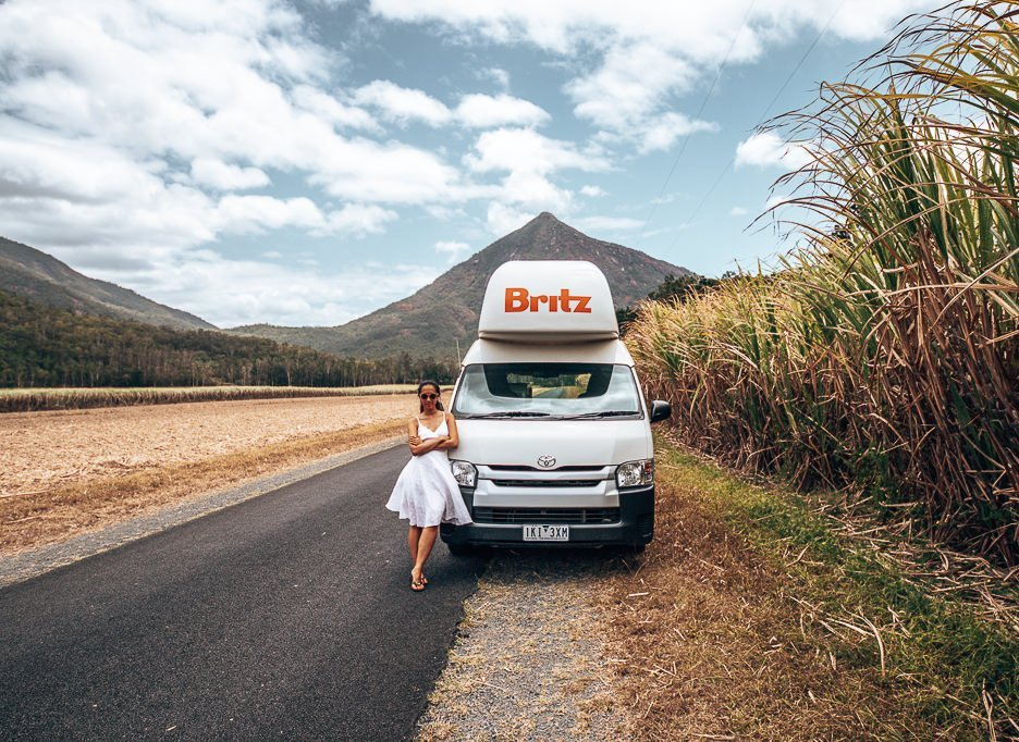A girl in a white dress stands next to a Britz campervan in Tropical North Queensland