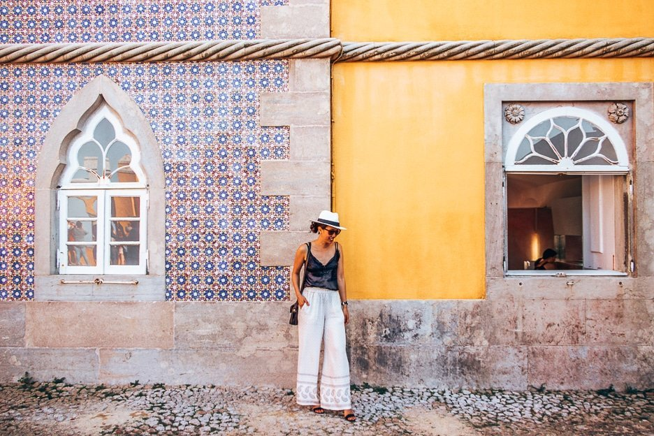 A woman poses in front of the yellow and blue walls of Pena Palace in Sintra, Portugal