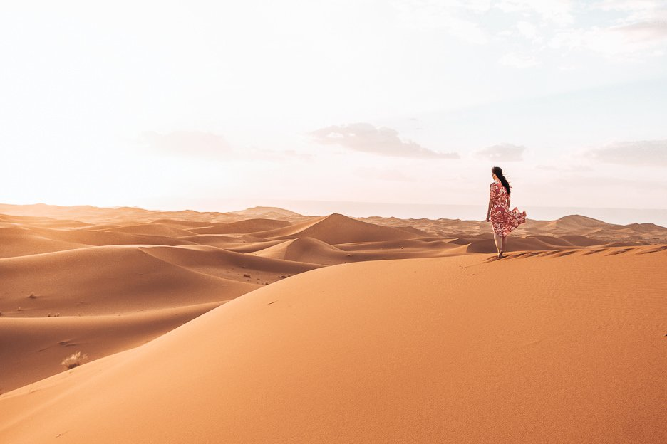 A woman in a red dress stands on a sand dune looking out into the distance in the Sahara Desert, Morocco
