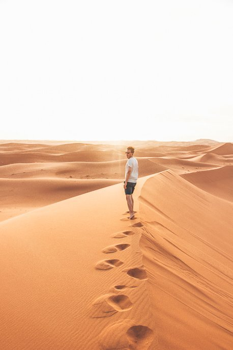 A man leaves footprints along a dune in the Sahara Desert, Morocco