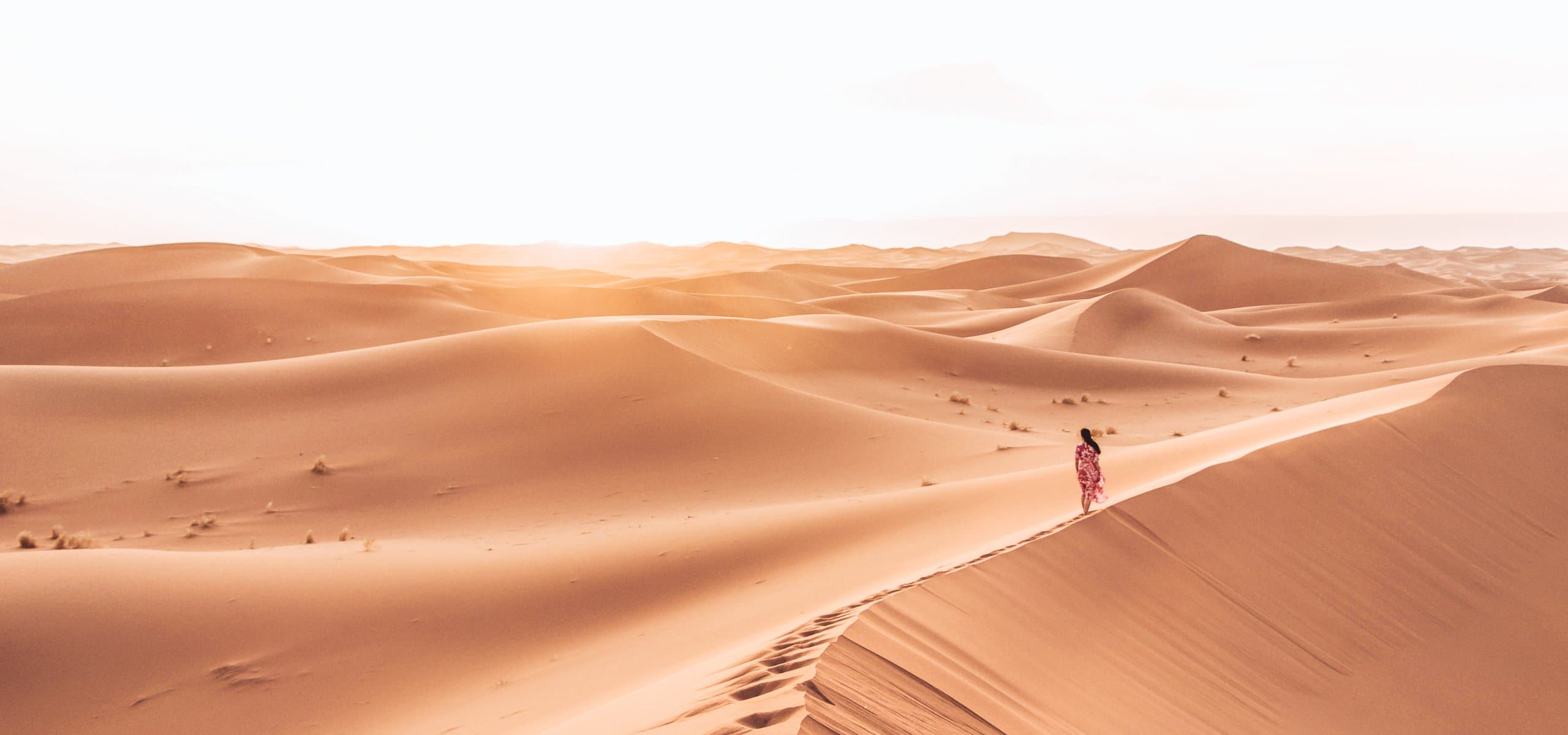 Jasmine walks along the peaks of a sand dune at sunset in the Sahara Desert, Morocco