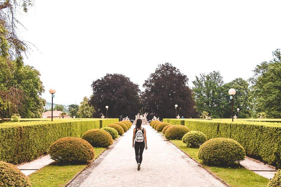 A girl with a white backback walks down a path with perfectly trimmed hedges, Zámecký park, Český Krumlov