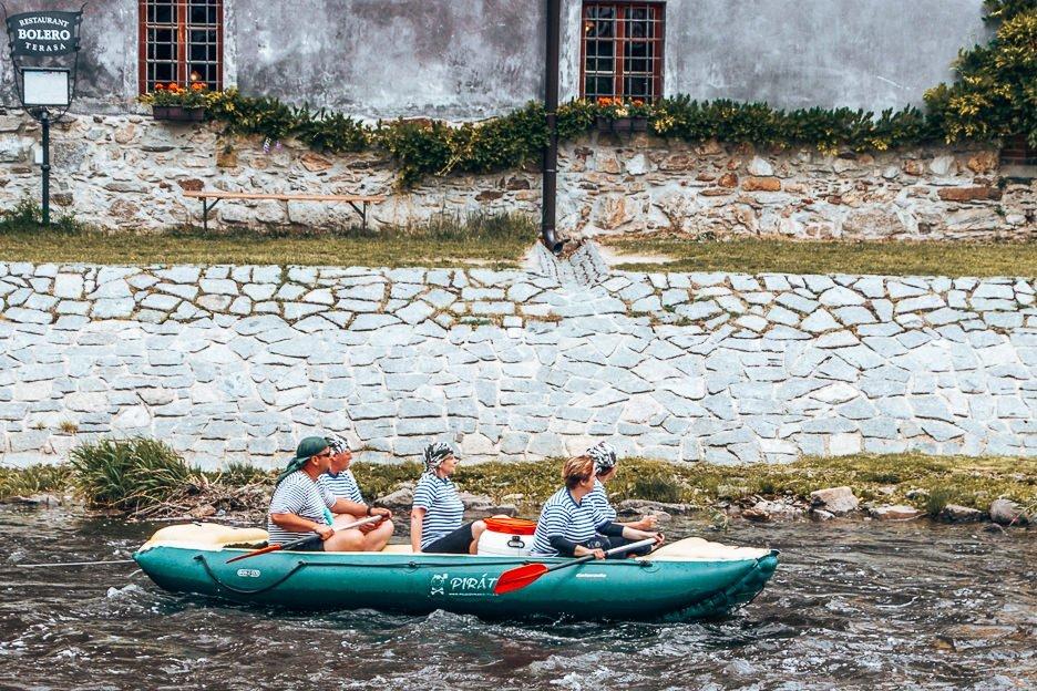 A green raft with 5 paddlers in stripey tshirts float along the Vlatva River, Český Krumlov