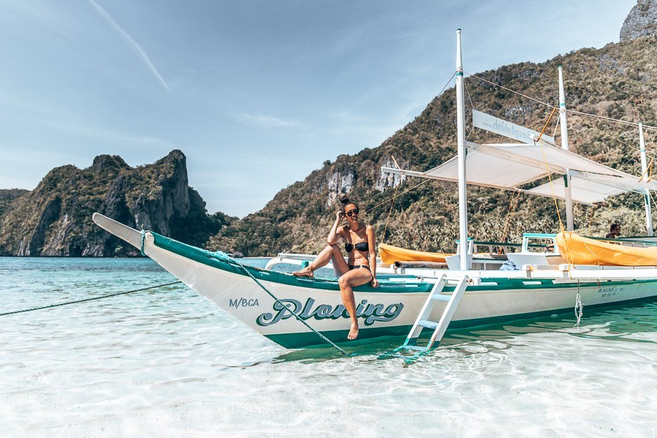 A girl in a black bikini and sunglasses sit smiling on the tour boat moored on an island in El Nido