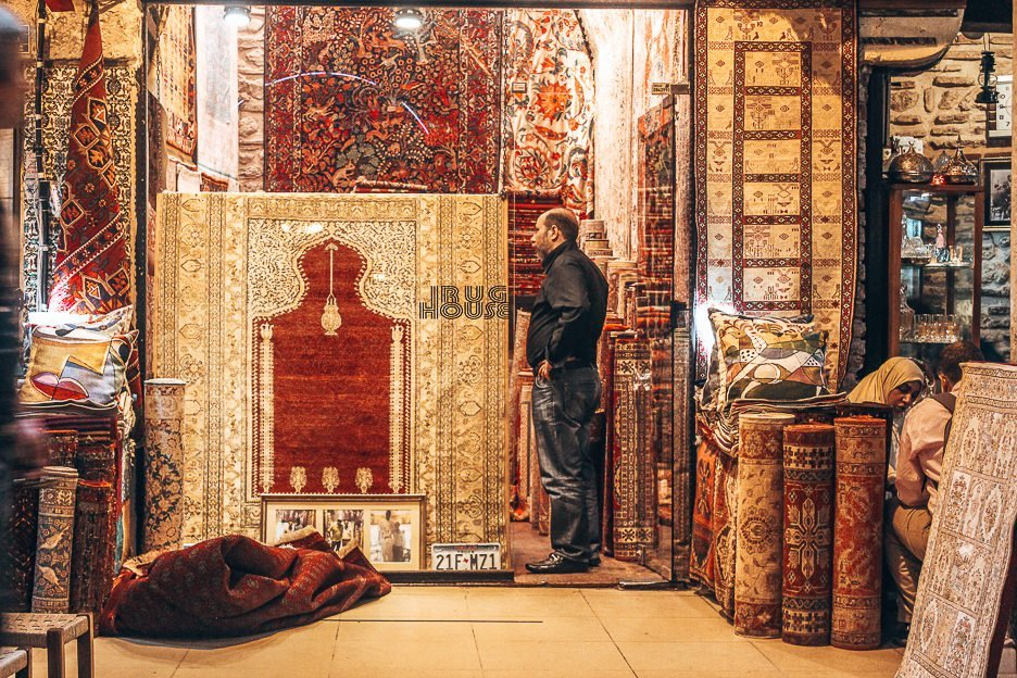 A man stands at the entrance of his rug shop inside the Grand Bazaar - Istanbul City Guide, Turkey