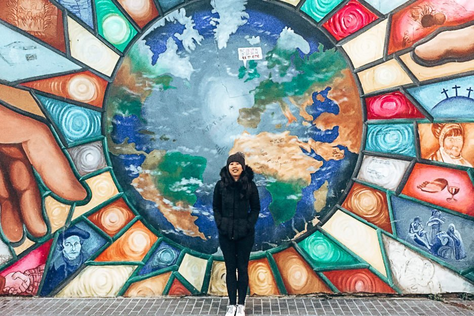 Jasmine stands in front of a Peace mural in Belfast, Northern Ireland