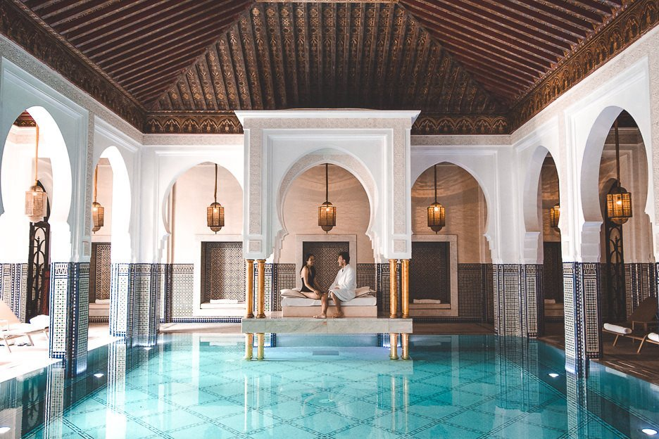 A couple sit on the day lounge in the indoor pool at La Mamounia, Marrakech, Morocco