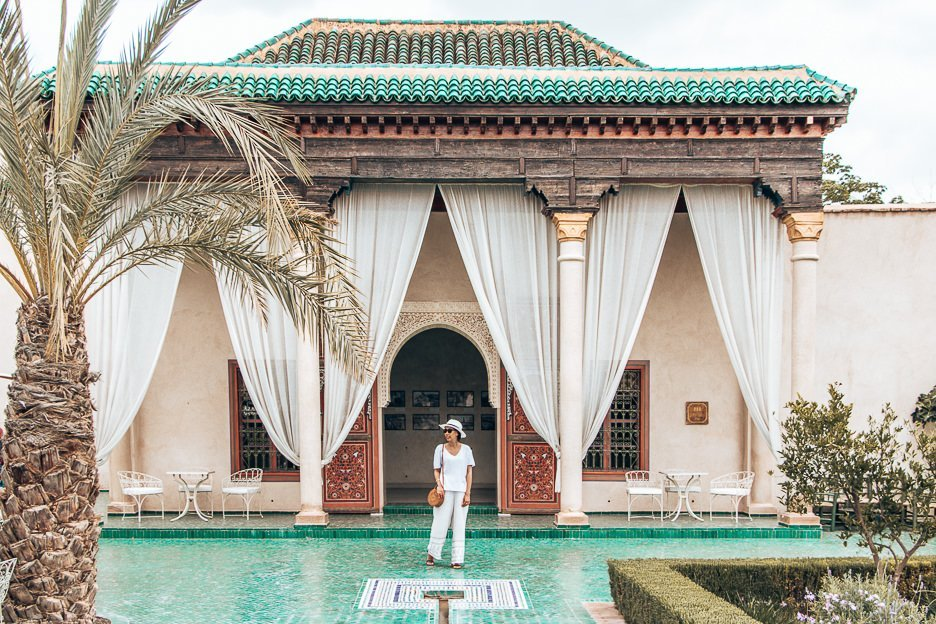 Jasmine stands on green tiles in between the white curtains of le Jardin Secret, Marrakech, Morocco