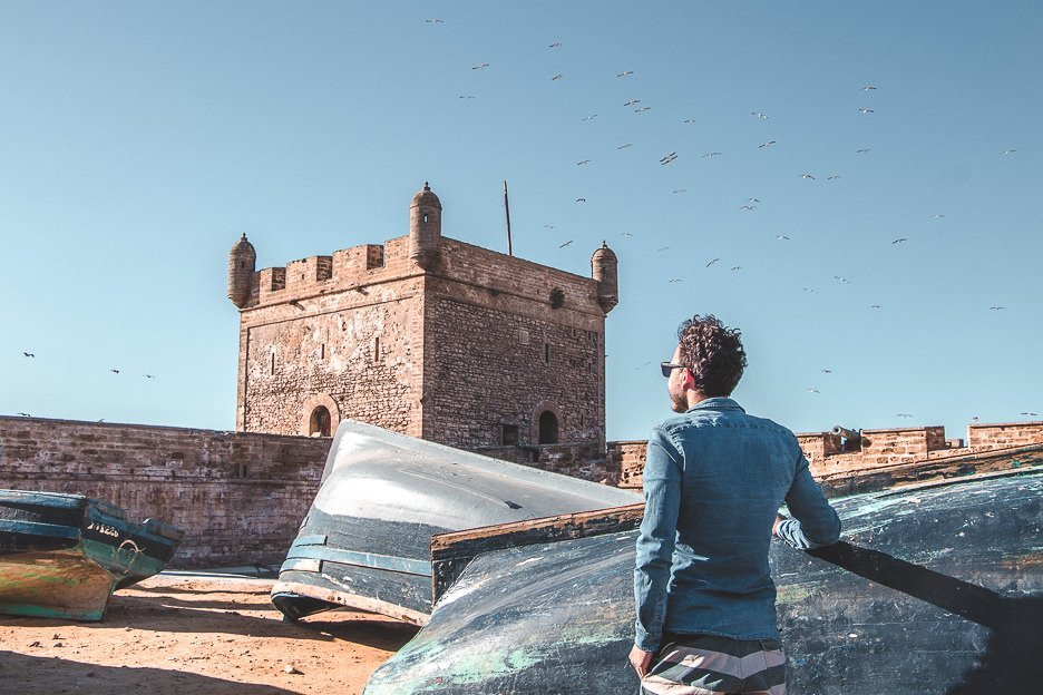 Bevan stands next to upturned blue fishing boats at Port of Essaouira, Morocco