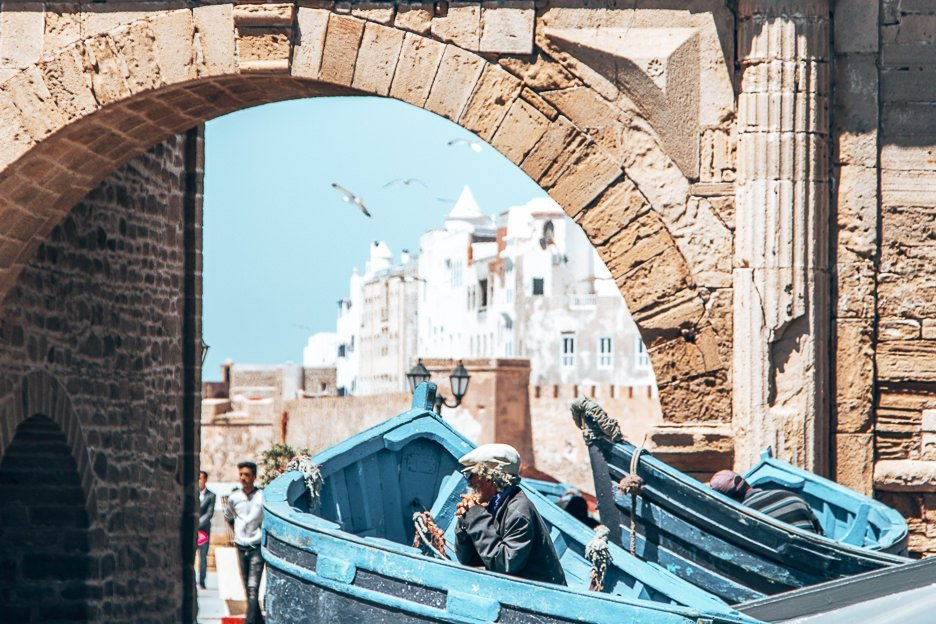 An old Moroccan man sits inside a blue boat ready to pose for photos for tourists at Essaouira harbour, Morocco