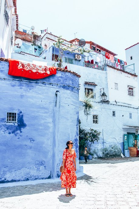 A woman dressed in a red dress stands in an empty square in Chefchaouen, Morocco