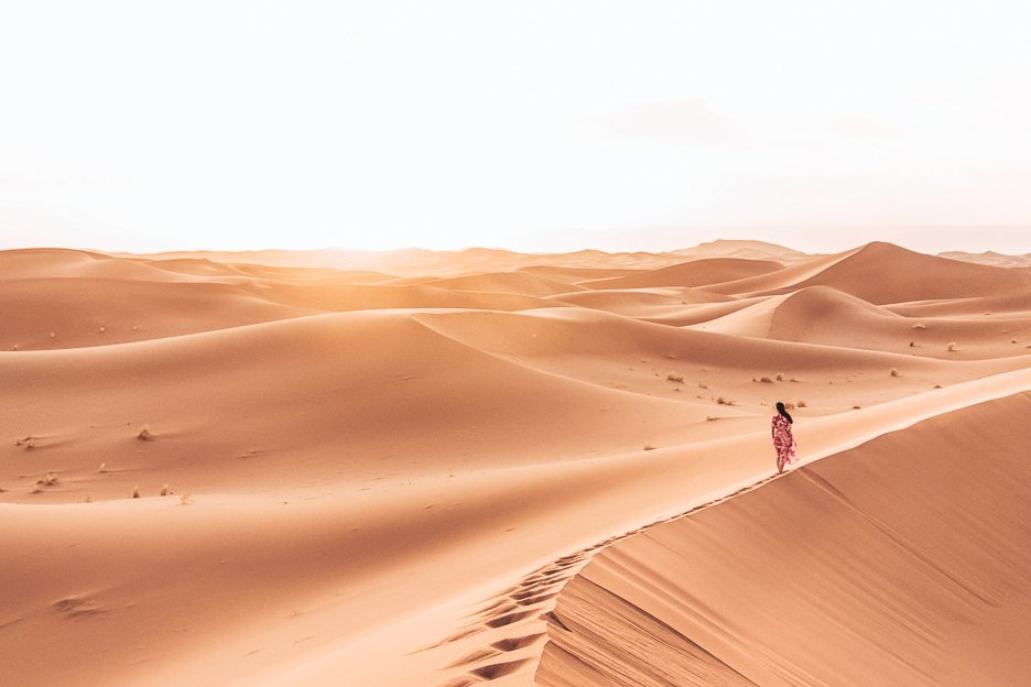 A woman in a red dress walks on the edge of a sand dune in the Sahara Desert, Morocco