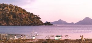 Boats sit on the shore of Nacpan Beach at sunset, El Nido, The Philippines