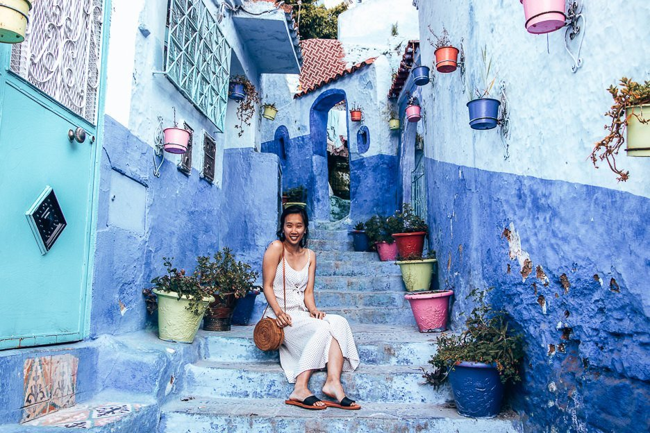 Jasmine of The Travel Quandary sits on the steps of a lane with coloured potted plants in Chefchaouen Morocco
