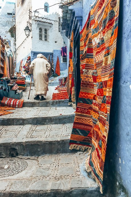 A Berber man walks up stairs past woven Moroccan rugs in Chefchaouen, Morocco