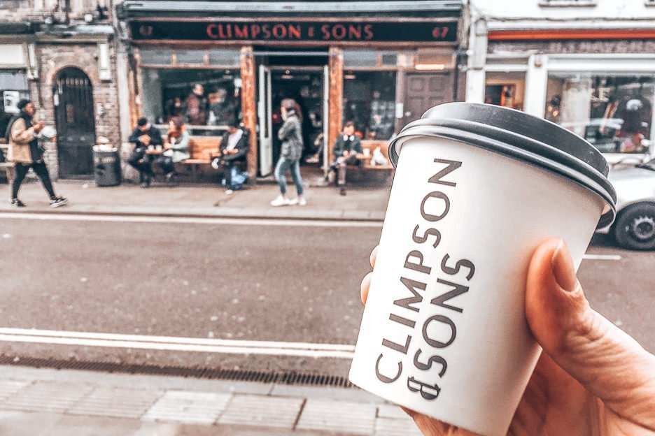 Holding a takeaway cup from Climpson & Sons in front of the Climpson & Sons cafe in East London