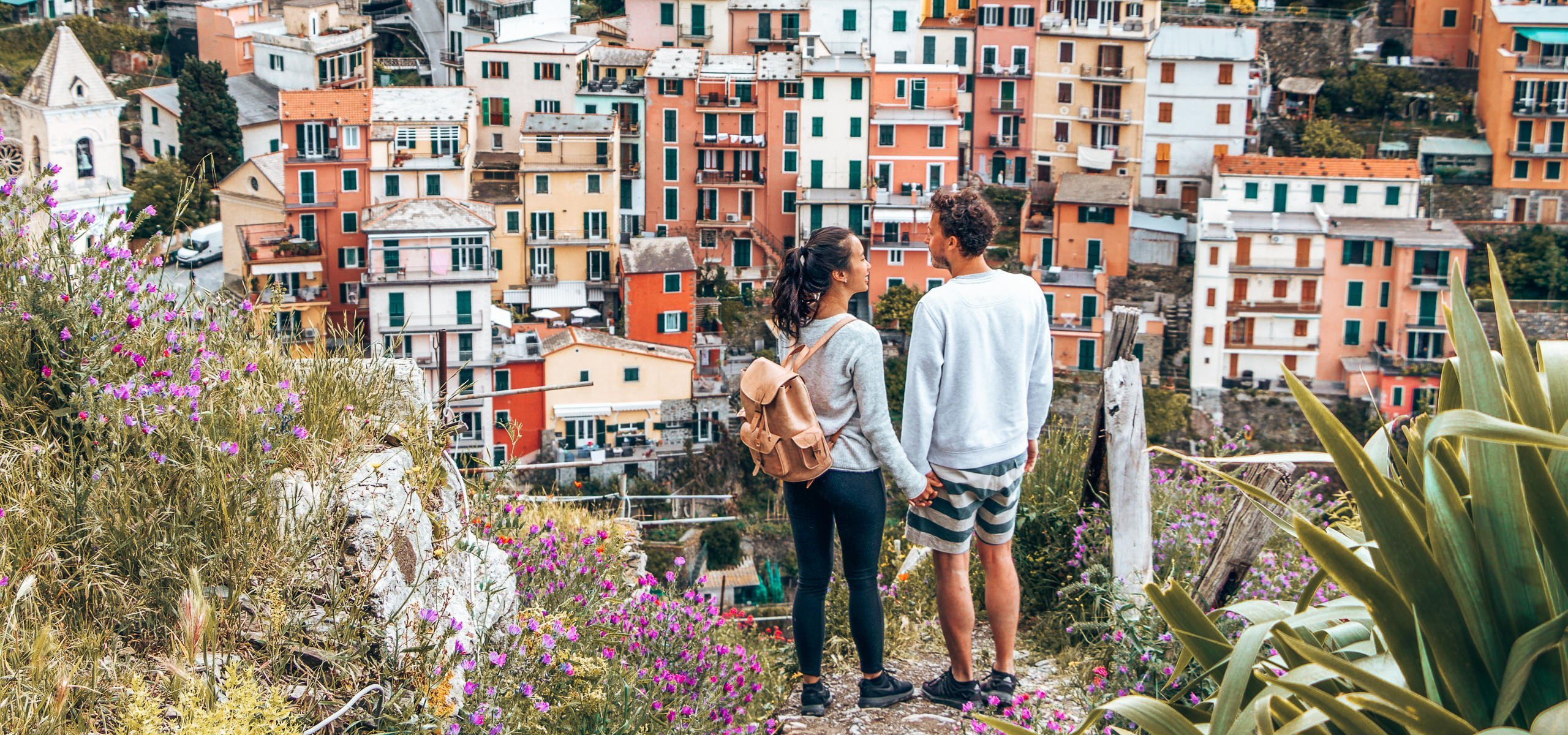 A couple holds hands overlooking the colourful houses of Manarola, Cinque Terre