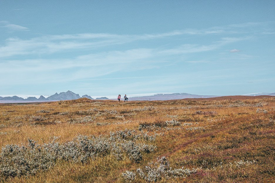 Campers wander through grassy plains, Iceland