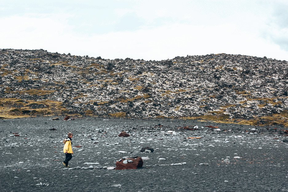 A women strolls across a black rocky beach, Iceland