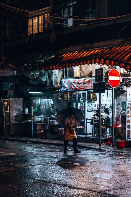 A woman carries a tray of food in the drizzly rain at night in Mong Kok, Hong Kong