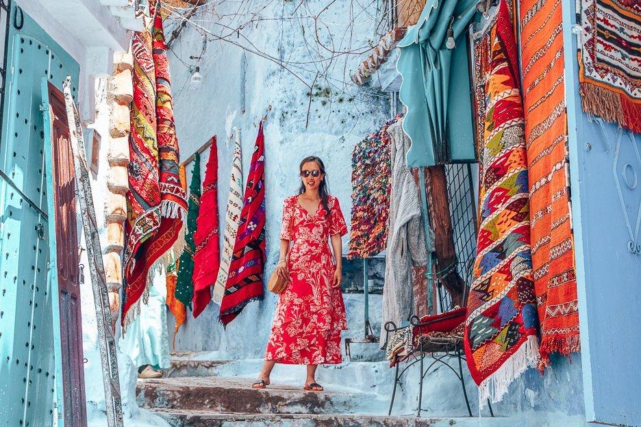 Jasmine of The Travel Quandary poses in front of woven Moroccan rugs for sale, Chefchaouen Morocco