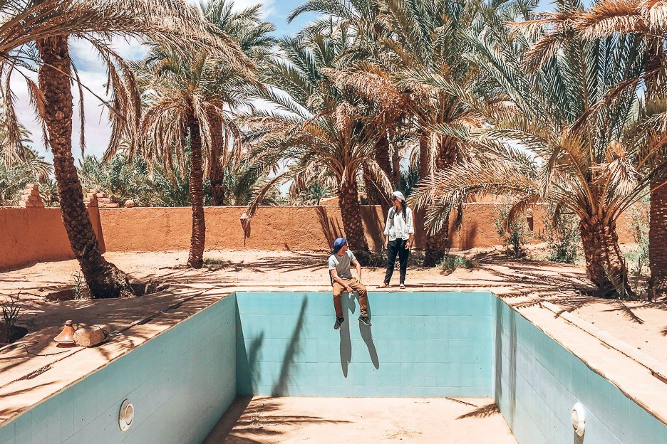 A man and a woman don Berber scarves and stand by an empty pool with palm trees in the Sahara Desert, Morocco