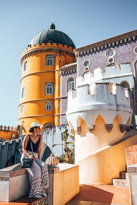 Jasmine sits on a ledge in front of blue and yellow towers at Pena Palace, Sintra- Lisbon