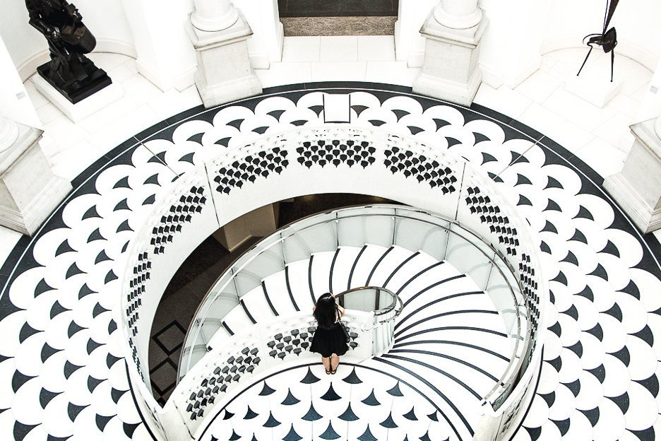 Jasmine of The Travel Quandary stands on top of the black and white marble staircase inside the Tate Britain in London - United Kingdom