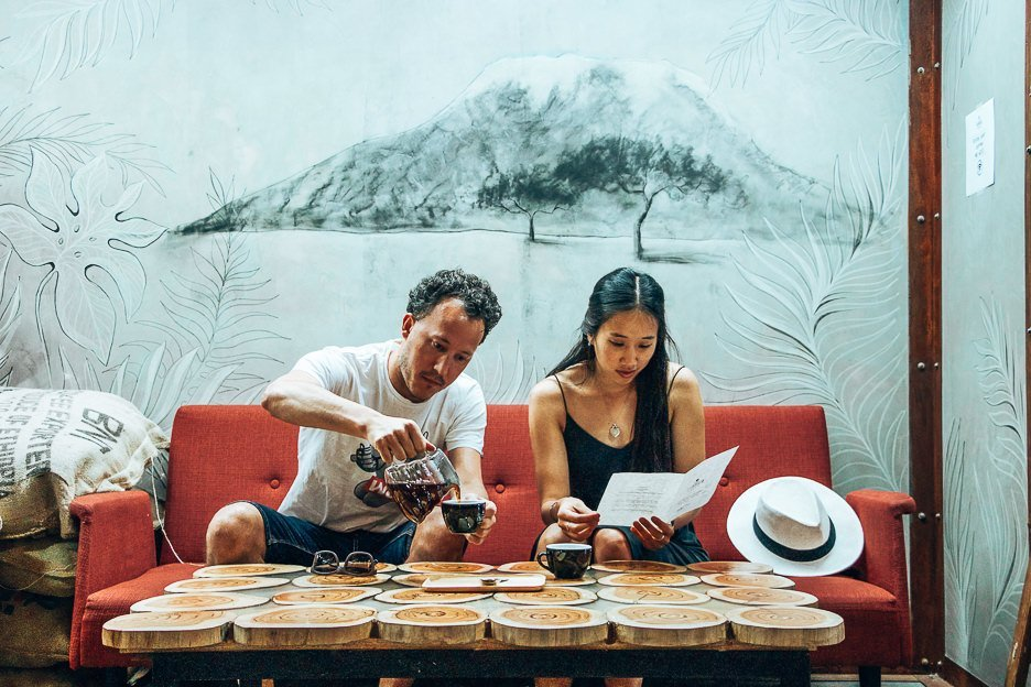 A man pours coffee while a woman reads the menu. Sitting on a red couch in Fabrica Coffee Roasters in Lisbon, Portugal