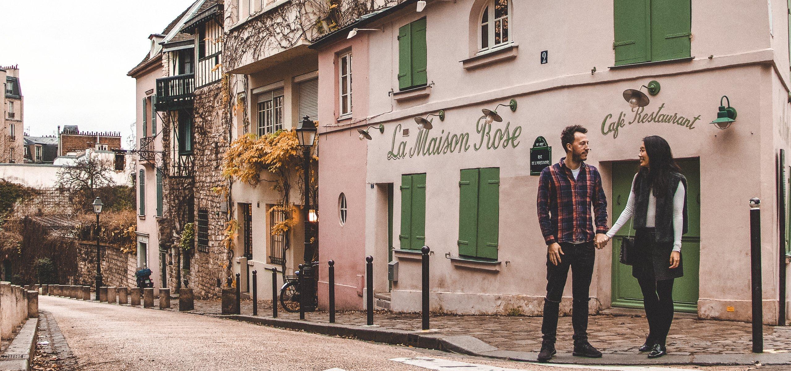 A couple holds hands In front of La Maison Rose, Montmartre, Paris - Travelling with Parents